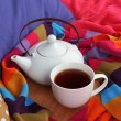 Stock Photo: Cup and teapot on wooden stand and scarf on bed close up