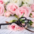 Stock Photo: Key of happiness. Conceptual photo. Key with roses, on light wooden background