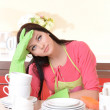 Beautiful young woman wipes clean utensils in kitchen — Stock Photo #38106015