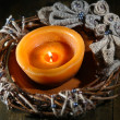 Burning candle with Christmas wreath on wooden background — Stock Photo
