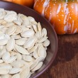 Pumpkin seeds in bowl with pumpkins on table close up — Stock Photo #38106701