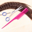 Long brown hair with comb and scissors on wooden background — Stock Photo #38107415