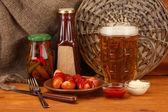 Bière et saucisses grillées sur une table en bois sur fond d'un sac — Photo