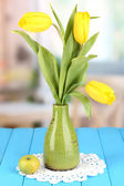 Yellow tulips in vase on wooden table on room background — Stock Photo