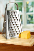 Metal grater and cheese on cutting board, on bright background — Stock Photo