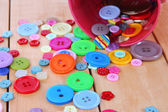 Colorful buttons strewn from bucket close-up — Stock Photo