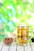 Beer in glass and croutons on table on nature background — Stock Photo