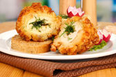 Chicken Kiev on croutons with mashed potatoes, on wooden table, on bright background — Stock Photo