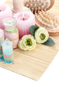 Aromatic salts in glass bottles and herbal compress balls for spa treatment, on bamboo mat, isolated on white — Stock Photo