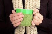 Cup with knitted thing on it in female hands close up — Stock Photo