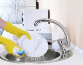 Close up hands of woman washing dishes in kitchen — Stok fotoğraf
