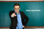Young teacher near chalkboard in school classroom — Stock Photo