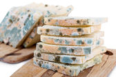 Mouldy bread on cutting board, isolated on white — Stock Photo