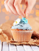 Confectioner decorating tasty cupcake with butter cream, on color wooden table, on lights background — Stock Photo