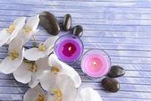 Beautiful colorful candles, spa stones and orchid flower,on color wooden background — Stock Photo