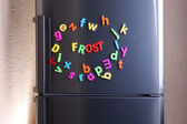 Word Frost spelled out using colorful magnetic letters on refrigerator — Stock Photo