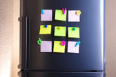 Empty paper sheets and colorful magnets on fridge door — Stock Photo