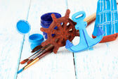 Hand made ceramic toys and color paints on wooden table — Stock Photo