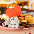 Sweet cookies with valentine card on plate on table in cafe — Stock Photo #38184201