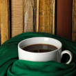 Cup of coffee wrapped in scarf on books background — Foto Stock #38184263