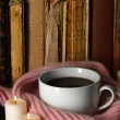 Cup of coffee wrapped in scarf on books background — Stock Photo