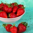 Strawberries in plate on blue background — Stock Photo
