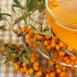Branches of sea buckthorn with tea on fabric background — Stockfoto