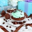 Stock Photo: Tasty cupcake with gifts close up