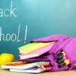 Purple backpack with school supplies on wooden table on green desk background — Stock Photo #38185857