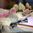 Composition with old book, eye glasses, candles and plaid on dark background — Stock Photo #38185931