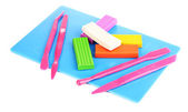 Children bright plasticine on desk with stacks isolated on white — Stock Photo