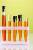 Tubos de ensayo con una solución de colorido en primer plano de fondo verde — Foto de Stock