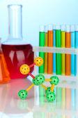 Model cząsteczki i probówek z kolorowych płynów na niebieskim tle — Zdjęcie stockowe