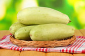 Fresh marrows on wicker mat, on wooden table, on bright background — Stock Photo