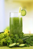 Glass of green vegetable juice and vegetables on bamboo mat on bright background — Stock Photo