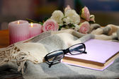 Composition with old book, eye glasses, candles and plaid on dark background — Stock Photo