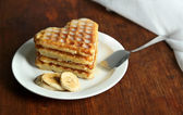 Sweet Belgium waffles with banana, on wooden table background — Stock Photo