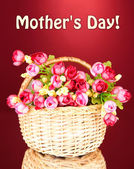 Bouquet of beautiful artificial flowers in wicker basket, on red background — Stock Photo