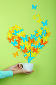 Paper butterflies fly out of cup on green wall background — Stock fotografie