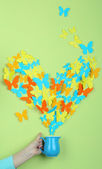 Paper butterflies fly out of pitcher on green wall background — Photo