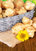 Topinambur roots in wicker basket on table close-up — Stock Photo