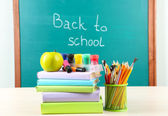 School supplies on table on blackboard background — Foto de Stock