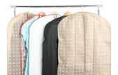 Clothes in cases for storing on hangers, isolated on white — Stock Photo