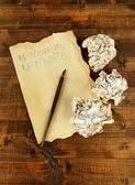 Crumpled paper balls with ink pen and music sheet on wooden background — Stock Photo