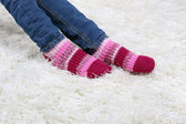 Female legs and colorful socks on white carpet background — Stock Photo
