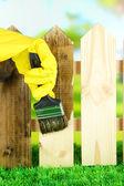 L'applicazione di vernice protettiva alla staccionata in legno, su sfondo luminoso — Foto Stock