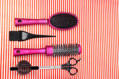 Hairdressing tools on striped red background — Stock Photo