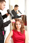 Young man hairdresser do hairstyle girl in beauty salon — Stock Photo