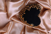 Decorative black heart, on color fabric — Stock Photo