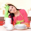 Beautiful young woman wipes clean utensils in kitchen — Stock Photo #38220237